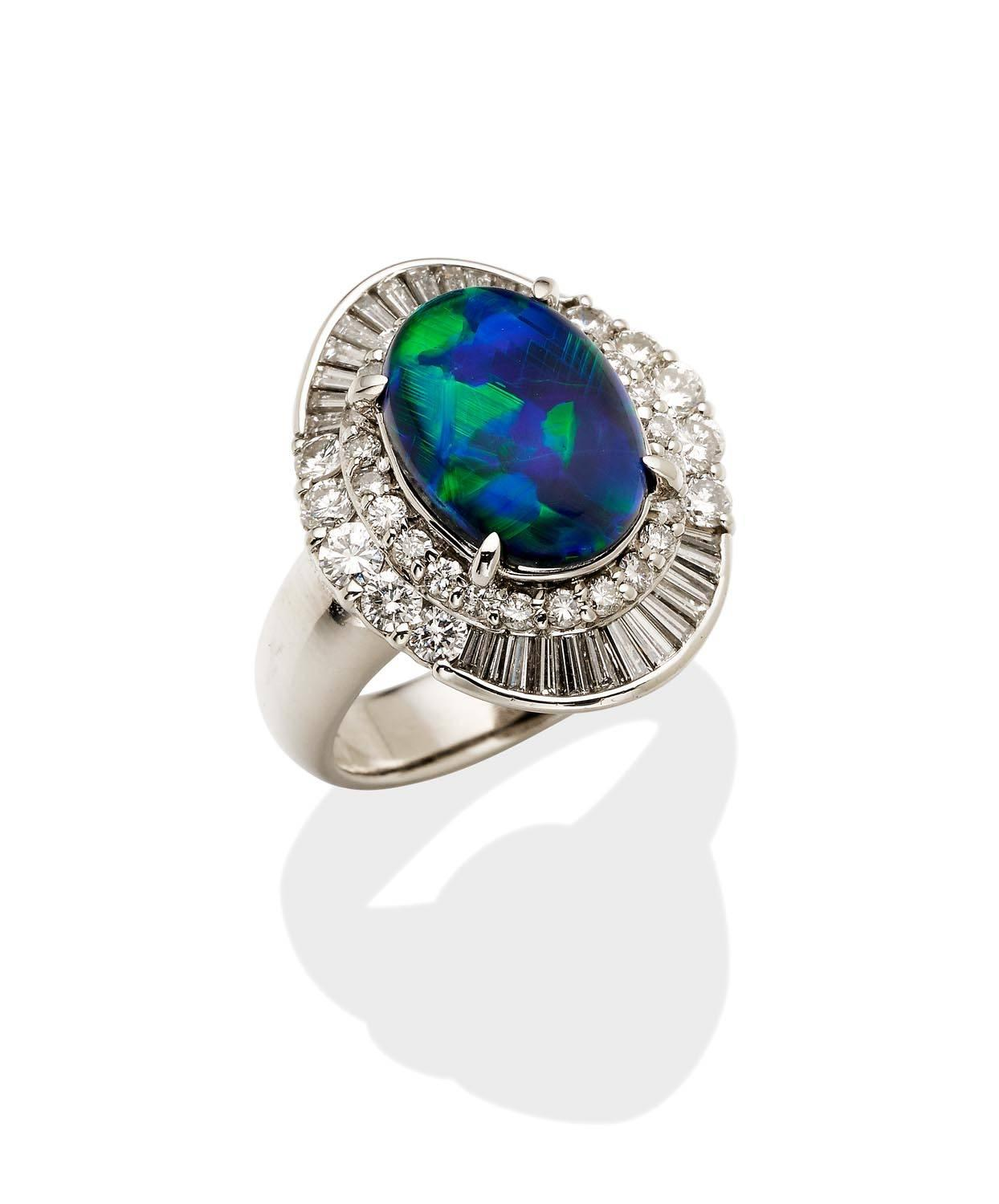 0ac058f67f30b1 Lot 113 of 298: An opal and diamond cluster ring, the central oval black  opal cabochon of known weight 2.55 carats, claw set above a stepped diamond  frame.